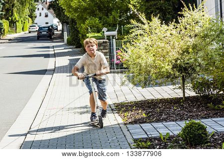 Boy Rides His Scooter At The Sidewalk