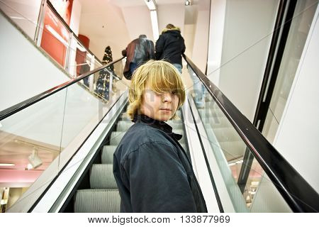 Child Is Smiling Self Confident On A Stairway In A Shopping Mall