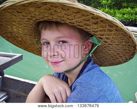 Boy Wearing A Hat Out Of Palmtrees For Sun Protection