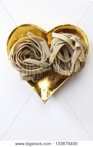 fettuccini dry pasta on the heart shape container