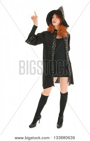 Young woman with red hair as evil witch pointing with finger isolated over white background