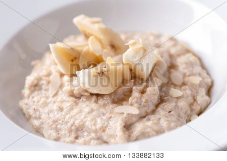 oatmeal porridge with banana  slices and almonds close-up on white plate