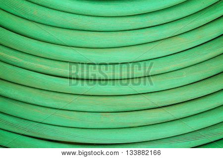 Meat water hose is coiled putting green.