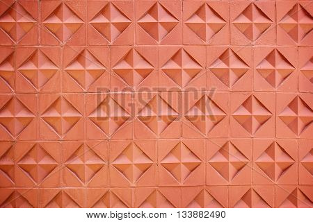 Brick wall with abstract floral pattern, brown for the background.