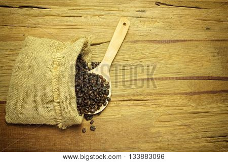 Coffee beans spilling from a burlap bag and a scoop on a textured wood surface