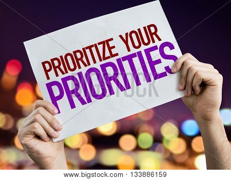 Prioritize Your Priorities placard with night lights on background