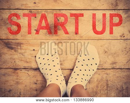 Selfie feet wearing white polka dot socks on with red print of the word start up on wooden floor background vintage filter effect