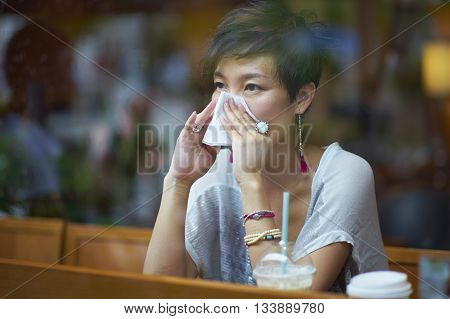 a sick young woman blowing her nose in coffee shop