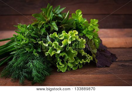 Variety Fresh Organic Herbs (lettuce, Arugula, Dill, Mint, Red Lettuce And Onion) On Wooden Backgrou