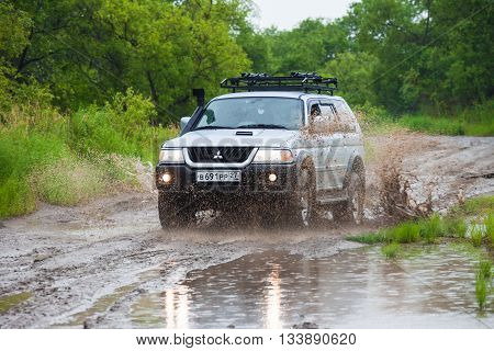 NIKOLAEVKA RUSSIA - JUNE 11 2016: Mitsubishi Pajero moving by water making lots of splashes