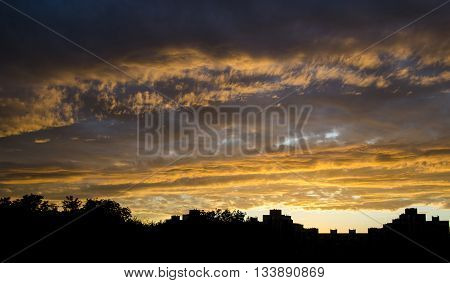 Stormy sky in fire of sunset and black outline cityscape. Burning clouds of coming storm