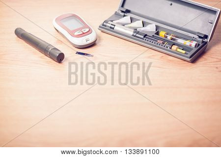 medicine diabetes advertisement and health care concept - close up of glucometer with blood sugar test stripe insulin injection syringes and pills on table