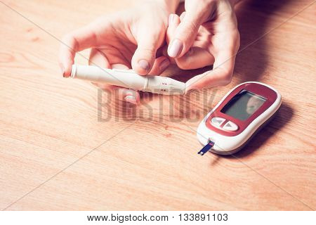 Close-up Of Woman Hands Testing High Blood Sugar With Glucometer Blood glucose meter The blood sugar value is measured on a finger Syringe pen with insulin and glucometer