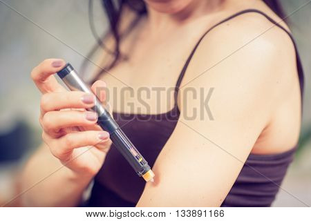 medicine diabetes glycemia health care and people concept - close up of woman with syringe making insulin injection to himself at home