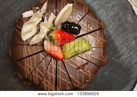 Triple layer chocolate cake on top with fresh fruit