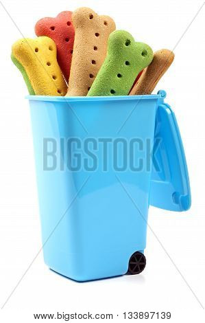 multi colored dog biscuits in a blue rubbish bin
