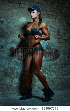 Woman with big muscles it is in underwear posing on wall background.