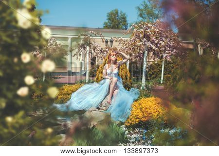 Girl in a long dress sitting in the park surrounded by flowers she observes.