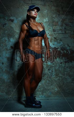 Woman with big muscles posing on wall background.