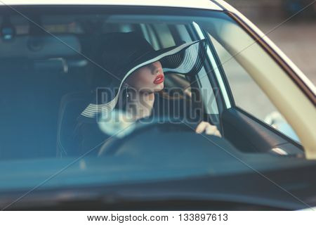 Woman in hat sitting behind the wheel of a car her lips bright red.