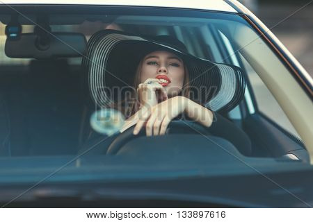 Woman in hat sitting behind the wheel of a car she sexually to his lips touched with a finger.