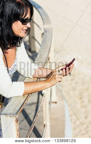 Side view of adult woman in sunglasses using phone while leaning on railings. Summertime.