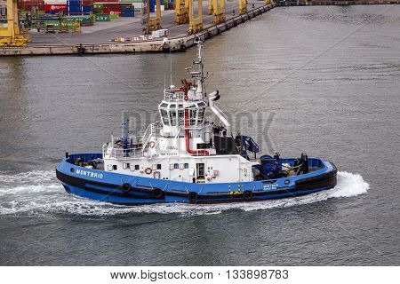 Barcelona Spain - September 26 2015: Tugboat Montbrio moving in international port of Barcelona built in 2007 with 29.5 m Length and 77 Tn pull Bolard