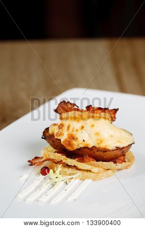 Hot rustic potato skins with cheese and bacon close-up on the table, vertical