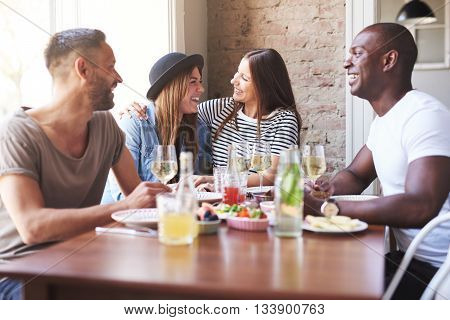 Woman Hugging Friend At Dinner Table