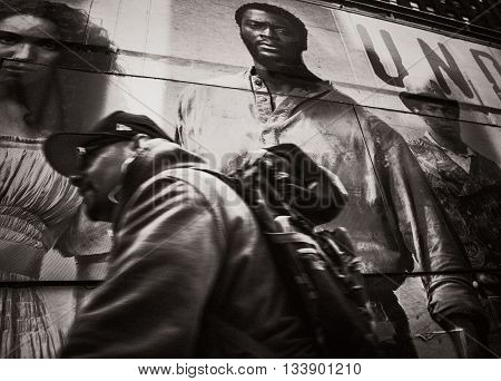 NEW YORK USA - Apr 28 2016: Street scene in midtwon Manhattan. Motion blurred black man against posters background on the streets of Manhattan. Old photo stylization film grain added. Sepia toned
