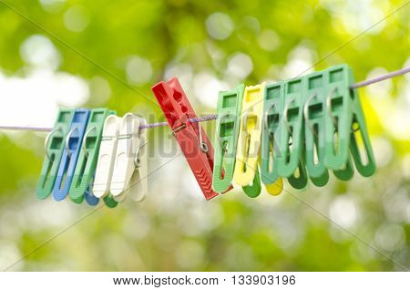 Plastic color clothespin hanging on rope isolated on green bokeh background. Close-up outdoor depth of field. Colorful clothes pegs set.