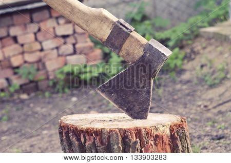 Axe carved in stump in courtyard on a brick background. Ax driven into the wood timber in the yard.