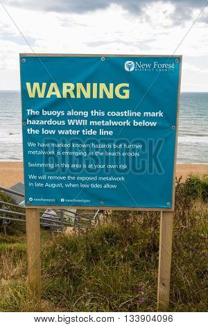 July 2015 sign warning of metal sea defences from second world war before metalwork removed at low tide.