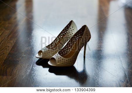 close up view of woman putting some shoe on shoes bride