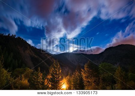 The starry sky with blurred motion clouds and bright moonlight captured from larch tree woodland glowing by burning fire. Expansive night landscape in the European Alps. Concept of adventure into the wild.