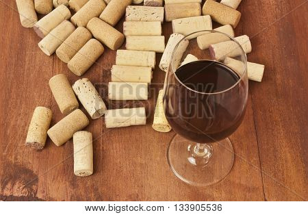 A photo of a glass of red wine with many different corks around it on a wooden boards background texture