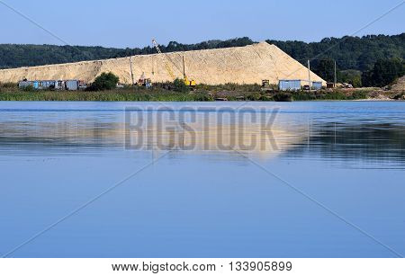 Sand extraction in the background on a flooded sand quarry