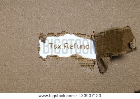 The word tax refund appearing behind torn paper.