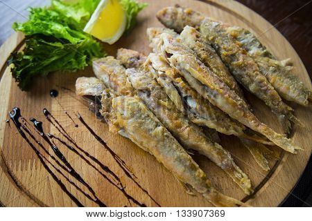 Fried red mullet fish on the plate, restaurant on the beach