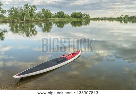 red stand up paddleboard with a paddle on calm lake ready for paddling workout - Arapaho Bend Natural Area, Fort Collins, Colorado