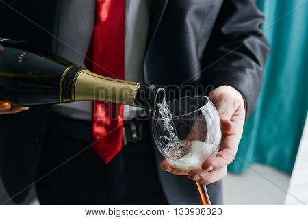 man filling decorated glass with champagne champagne glass hand