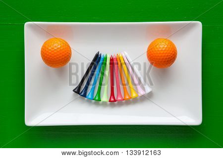 White ceramic dishes with golf wooden tees and white balls on over green background rectangle dish