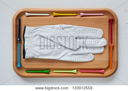 Cutting board with different wooden golf tees and white glove