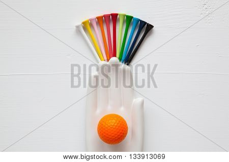 Detail of ceramic hand with golf balls and tees on the white wooden desk - Flat Lay Photography