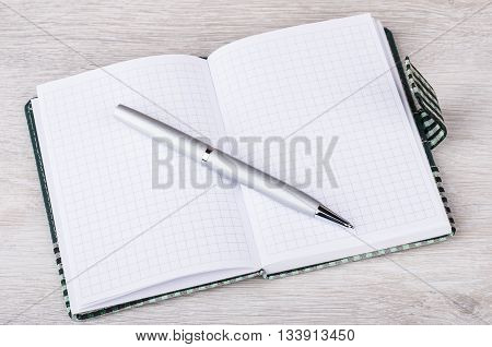 Open notebook and ballpoint pen on wooden table