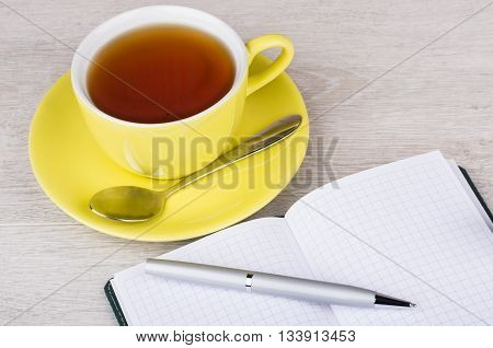 Cup Of Tea, Open Notebook And Ballpoint Pen