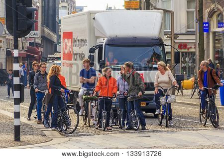 AMSTERDAM, NETHERLANDS - MAY 7, 2013: Group of tourists on bikes discusses his further route at the crossroads.