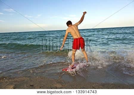 teenage boy learning surfing at the beach