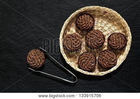 Chocolate mini cakes in a wicker basket and tongs for pastries on slate background with space for text