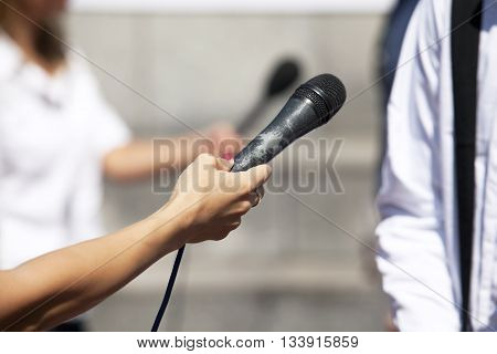 News. Reporter holding a microphone conducting an TV or radio interview